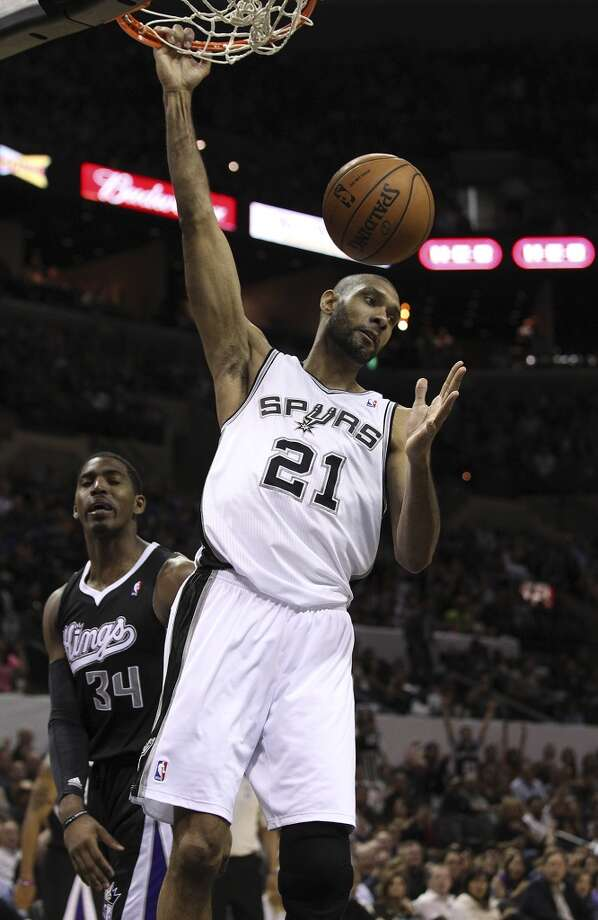 The Spurs\' Tim Duncan (21) dunks against Sacramento Kings\' Jason Thompson (34) in the second half at the AT&T Center on Friday, Apr. 12, 2013. Spurs defeated the Kings, 108-101.