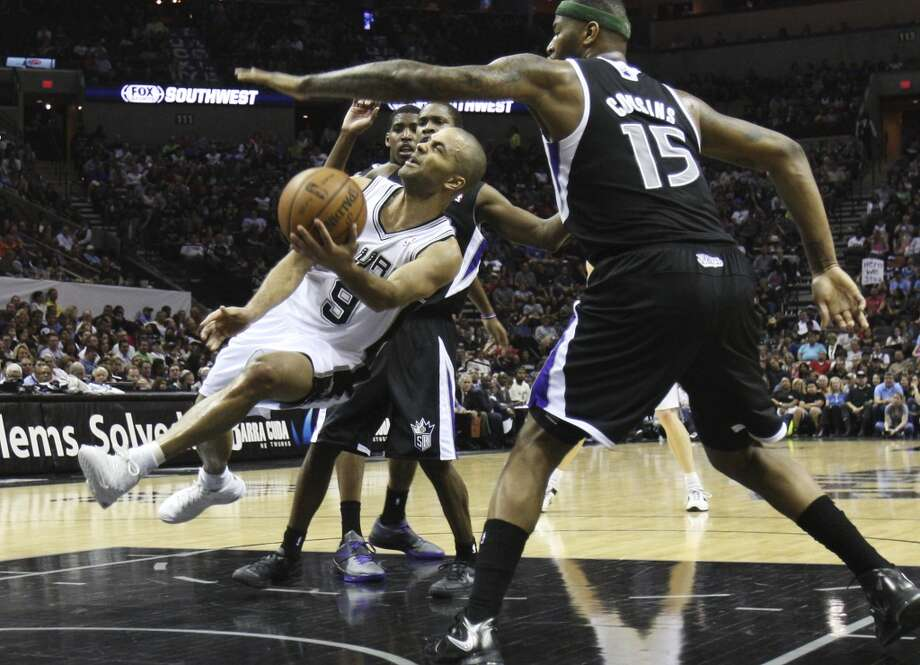 The Spurs\' Tony Parker (9) attempts a shot against Sacramento Kings\' DeMarcus Cousins (15) in the second quarter at the AT&T Center on Friday, Apr. 12, 2013.