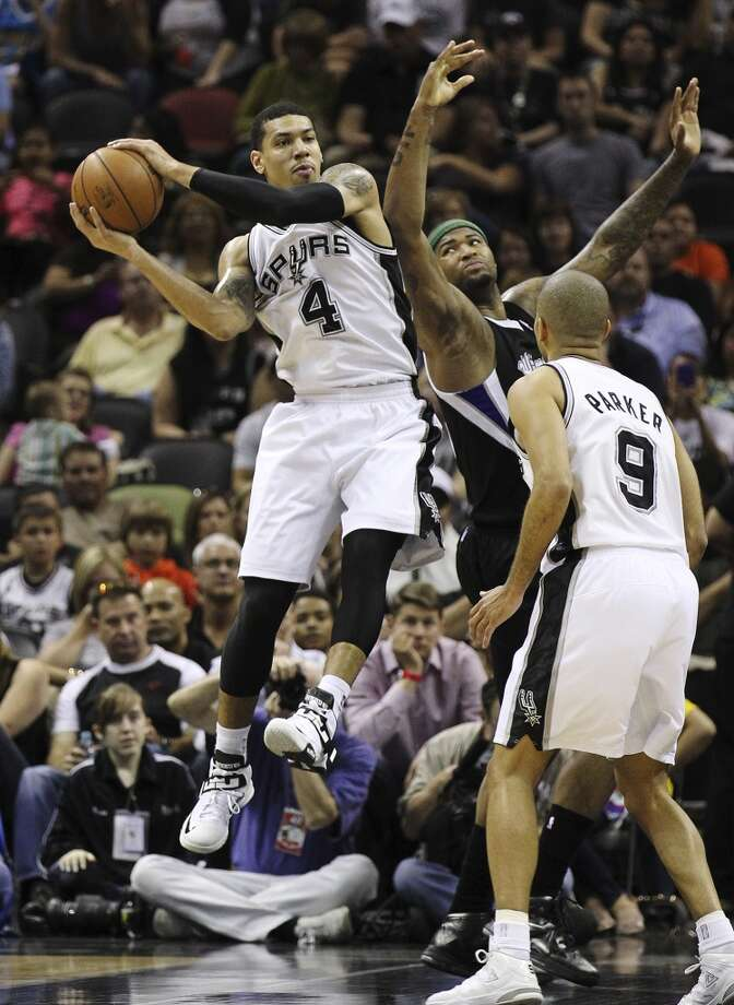 The Spurs\' Danny Green (4) grabs a rebound against Sacramento Kings\' DeMarcus Cousins (15) in the first quarter at the AT&T Center on Friday, Apr. 12, 2013.