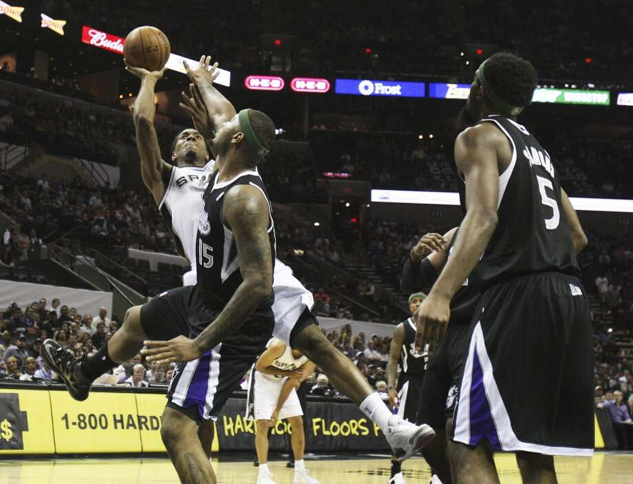 The Spurs\' Kawhi Leonard (2) fades back for a shot against Sacramento Kings\' DeMarcus Cousins (15) in the first quarter at the AT&T Center on Friday, Apr. 12, 2013.
