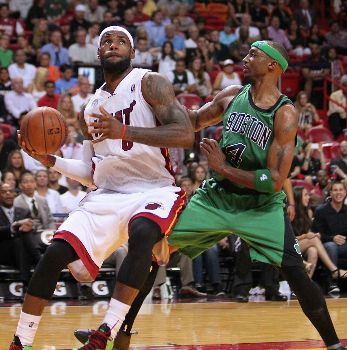 LeBron James, left, goes to the basket despite the best defensive efforts of the Celtics' Jason Terry during fourth-quarter action Friday night in Miami.