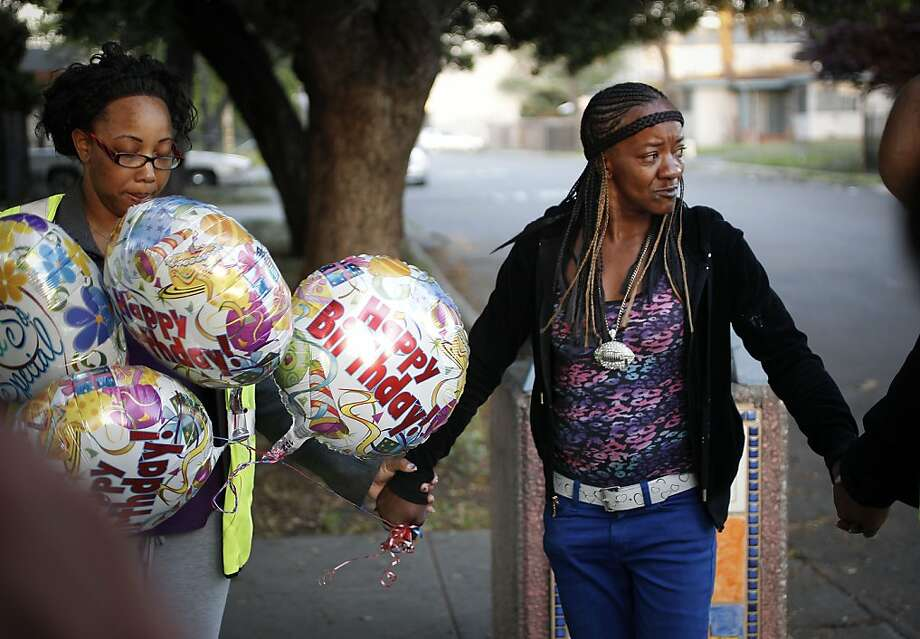 Daphnie Banks (right) stops to pray with members of the Ceasefire program on the street corner in Richmond where her 22-year-old son was killed a year ago. Photo: Michael Macor, The Chronicle