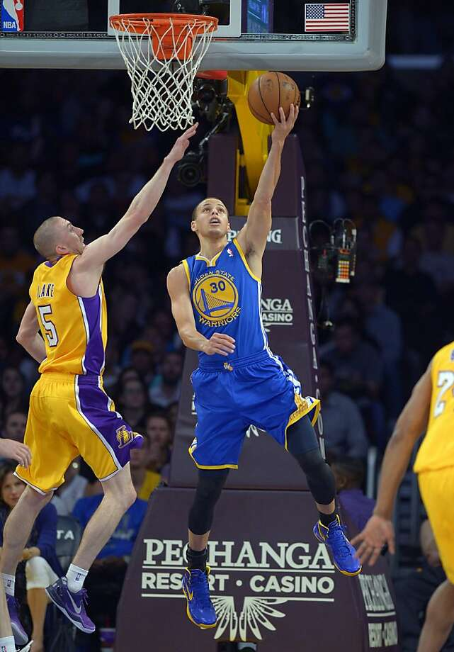 The Lakers' Steve Blake tries to stop Stephen Curry's layup during the first half. Curry scored 22 of his 47 points in the first quarter. Photo: Mark J. Terrill, Associated Press