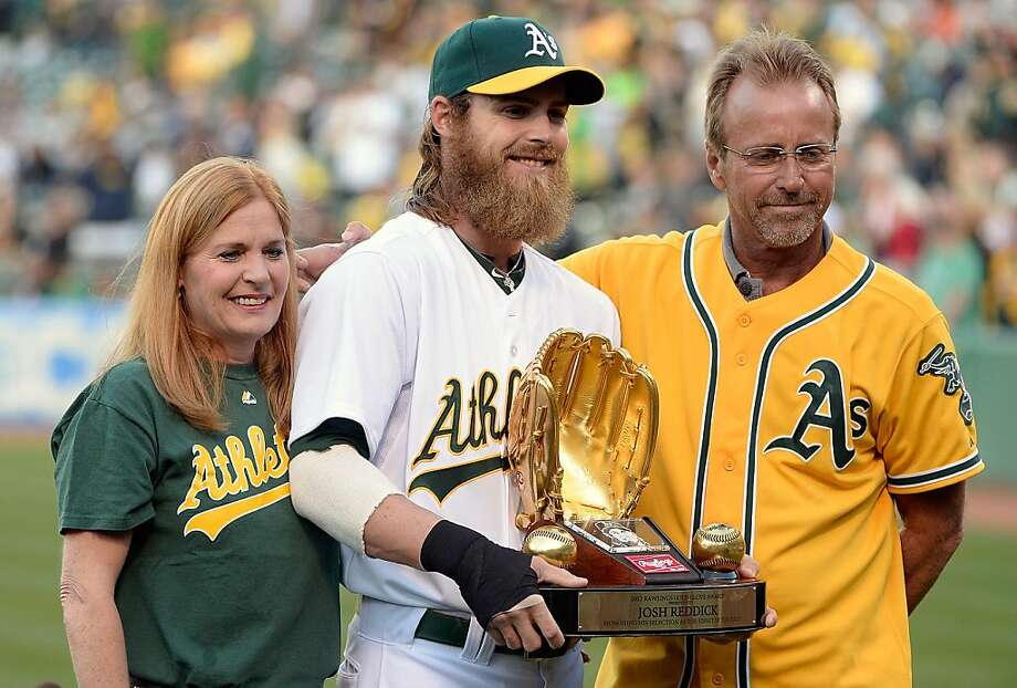 Josh Reddick had plenty of family on hand as he became the first A's outfielder to get a Gold Glove since Dwayne Murphy. Mother Cheryl (left) and father Kenny (right) were on hand. Photo: Thearon W. Henderson, Getty Images