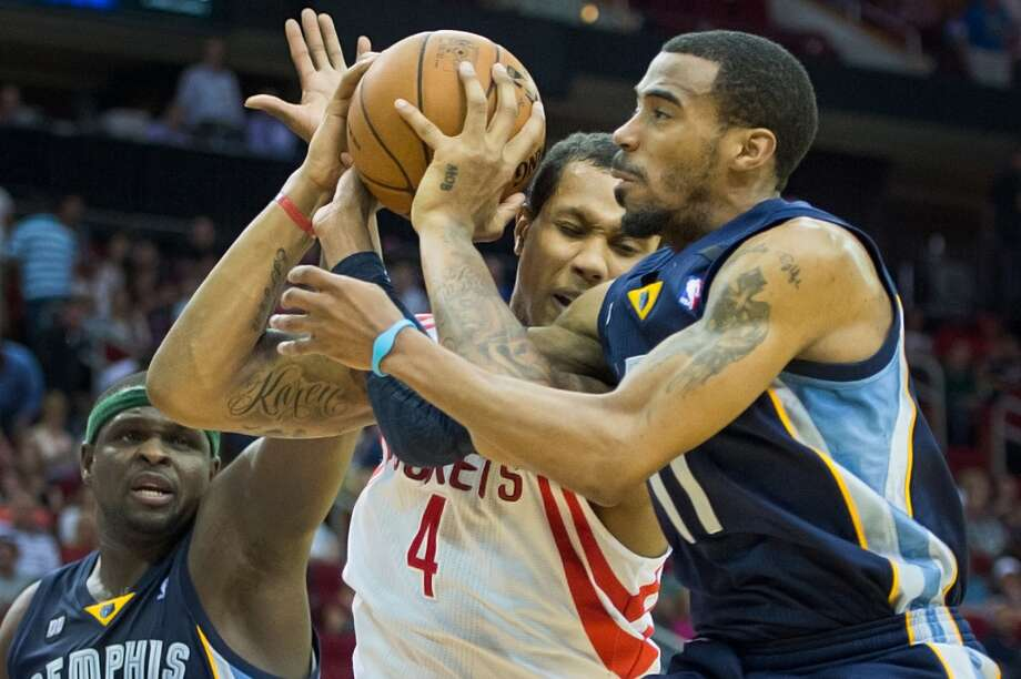 Rockets power forward Greg Smith (4) struggles with Grizzlies point guard Mike Conley for a rebound.