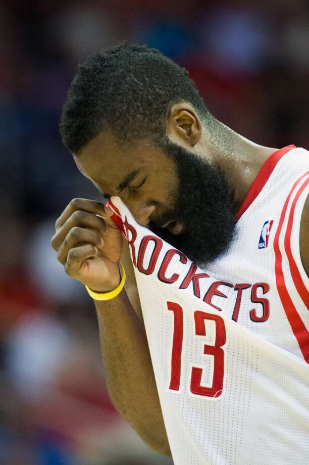 Rockets guard James Harden holds his right eye after being poked by a Grizzlies player during the first half.