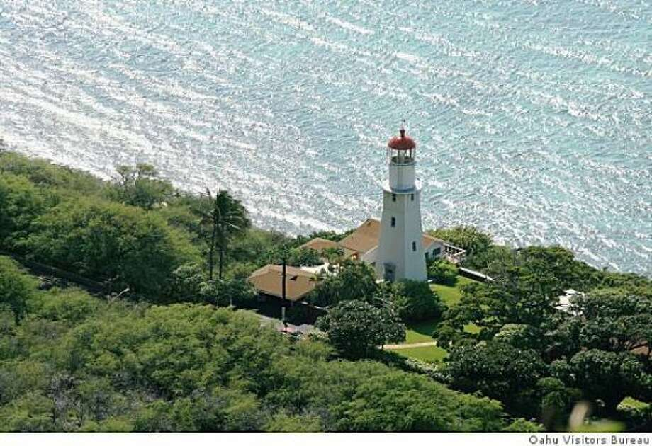 The Diamond Head Lighthouse stands guard below the famous crater on O'ahu\'s southeast shore.