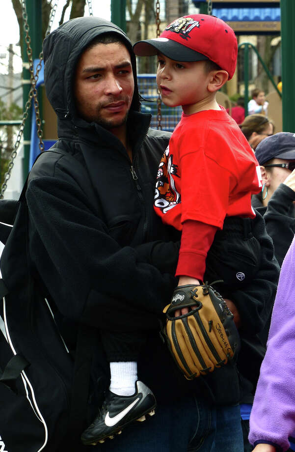 Michael Cruz holds his son Jeremiah, 4, who is on the Muckdogs t-ball team before the start of the Opening Day Ceremony which was held for teams in the Black Rock Little League at Ellsworth Field in Bridgeport, Conn. on Saturday April 13, 2013. Photo: Christian Abraham / Connecticut Post