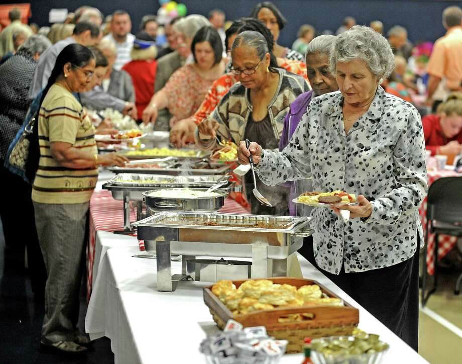Laura Blackwell, right, leads the line at the Breakfast with the Bishop fundraiser to benefit Catholic Charities of Southeast Texas on Saturday, April 13, 2013, at Saint Jude Thaddeus Catholic Church. Photo taken: Randy Edwards/The Enterprise