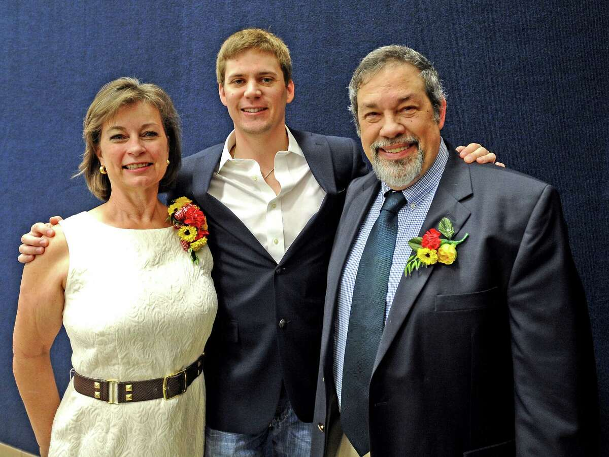 Humanitarian Award honorees Karen and Mike Fuljenz stand with their son Jake, center, at the Breakfast with the Bishop fundraiser to benefit Catholic Charities of Southeast Texas on Saturday, April 13, 2013, at Saint Jude Thaddeus Catholic Church. Photo taken: Randy Edwards/The Enterprise
