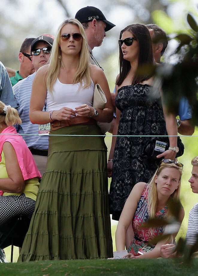 Skier Lindsey Vonn, second right, and her physical therapist Lindsay Winninger watch Tiger Woods during the third round of the Masters golf tournament Saturday, April 13, 2013, in Augusta, Ga. (AP Photo/David Goldman) Photo: David Goldman, Associated Press / AP