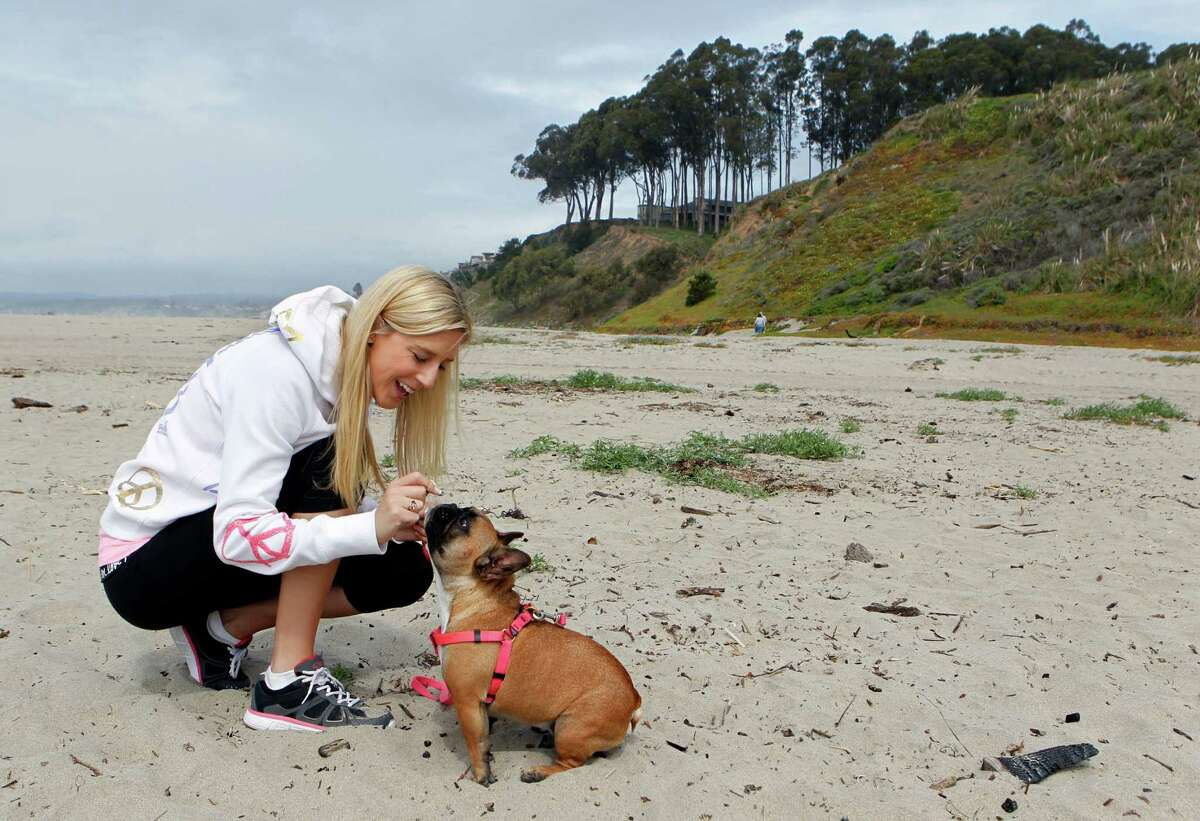 Brooke Stone offers a treat to her dog while on the beach in Aptos, Calif. Stone is regaining her strength after undergoing open heart surgery last September.