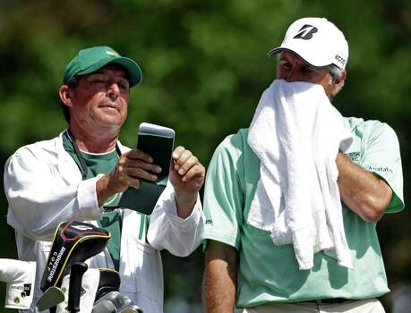 Fred Couples checks his course notes with his caddie David Kerr on the fourth tee during the third round of the Masters golf tournament Saturday, April 13, 2013, in Augusta, Ga. (AP Photo/Darron Cummings) Photo: Darron Cummings, Associated Press / AP