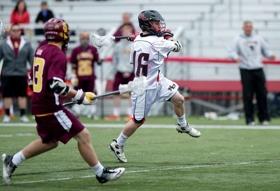 New Canaan's Harry Stanton takes a shot and scores a goal during Saturday's boys lacrosse game against St. Joseph at New Canaan High School on April 13, 2013. Photo: Lindsay Perry / Stamford Advocate