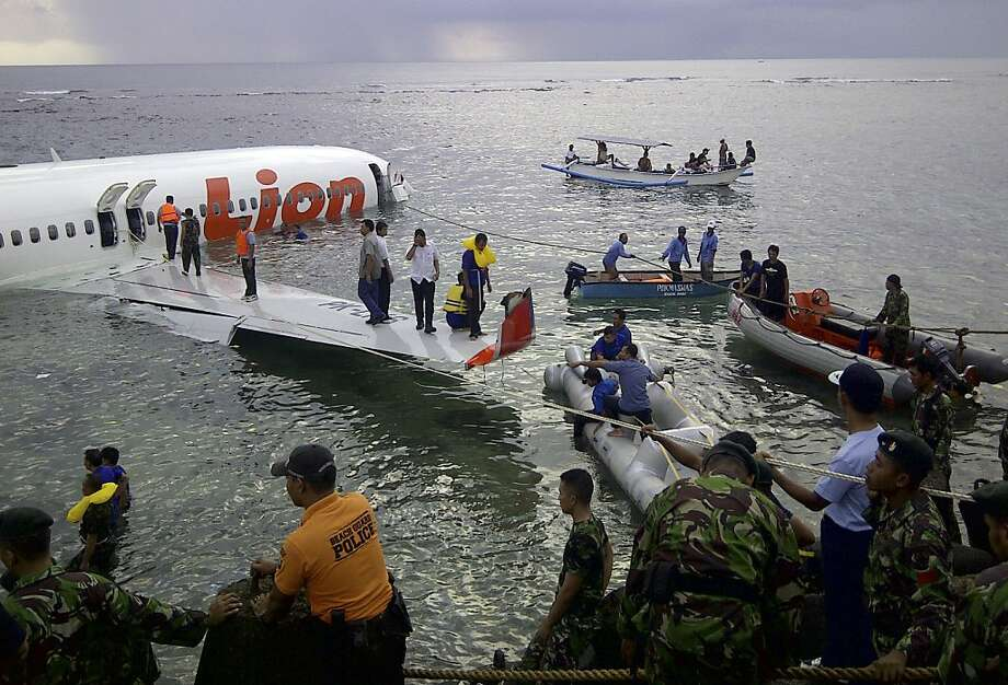 Rescuers help passengers and crew leave an airplane that crashed off the resort island of Bali. Photo: Associated Press
