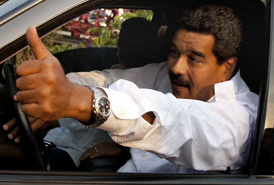 Venezuela's interim President Nicolas Maduro gives a thumbs up as Argentina's soccer legend Diego Armando Maradona sits behind him as they leave after paying their respects at the tomb of late President Hugo Chavez in Caracas, Venezuela, Friday, April 12, 2013. Maduro, who served as Chavez's foreign minister and vice president, is running against opposition candidate Henrique Capriles in Sunday's presidential election to replace Chavez who died on March 5. (AP Photo/Ramon Espinosa) Photo: Ramon Espinosa, Associated Press