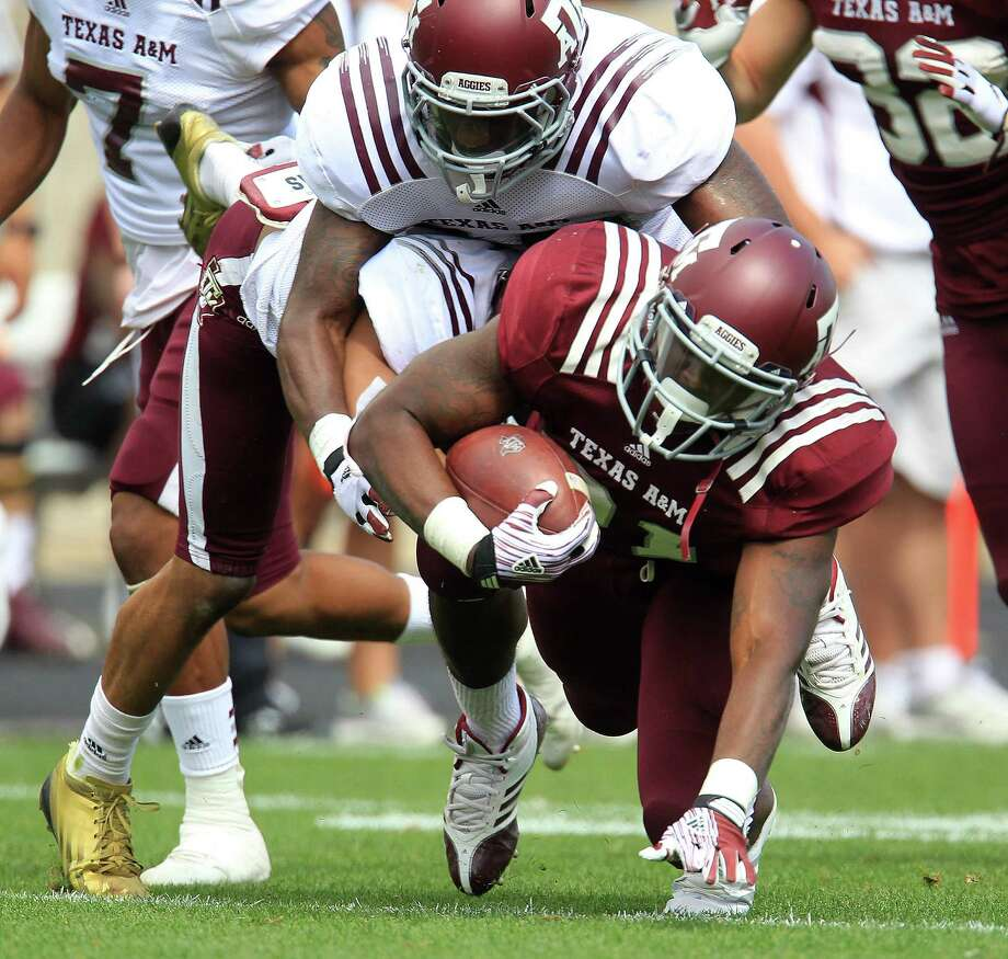 Texas A&M Aggies running back Tra Carson (21) is tackled by teammates during the second half of the Texas A&M University's Maroon & White, spring game at Kyle Field, Saturday, April 13, 2013, in College Station. Photo: Karen Warren, Houston Chronicle / © 2013 Houston Chronicle