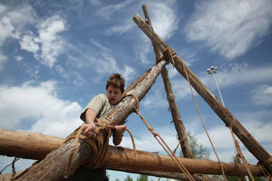 """Blake Dozier, 12, of Tomball Boy Scout Troop #41, helps secure a bridge while his troop work on their Pioneering Skills by making a bridge out of wood and rope during the Scout Fair 2013, """"The Best Scout Fair on Earth"""", at Reliant Arena on Saturday, April 13, 2013, in Houston. Photo: Mayra Beltran, Houston Chronicle / © 2013 Houston Chronicle"""