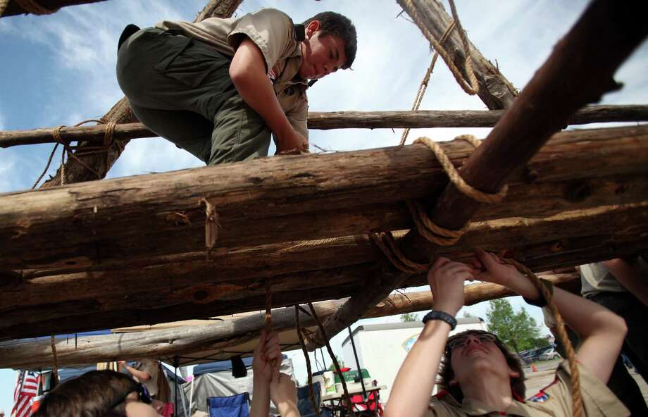 "Anthony Pucci, 16, of Tomball Boy Scout Troop #41, stands on the bridge to receive rope and fellow troop members Preston McMath, 14, and Hunter Ash, 14, tie the rope while building a Log Bridge by using their Pioneering Skills during the Scout Fair 2013, ""The Best Scout Fair on Earth"", at Reliant Arena on Saturday, April 13, 2013, in Houston. Photo: Mayra Beltran, Houston Chronicle / © 2013 Houston Chronicle"