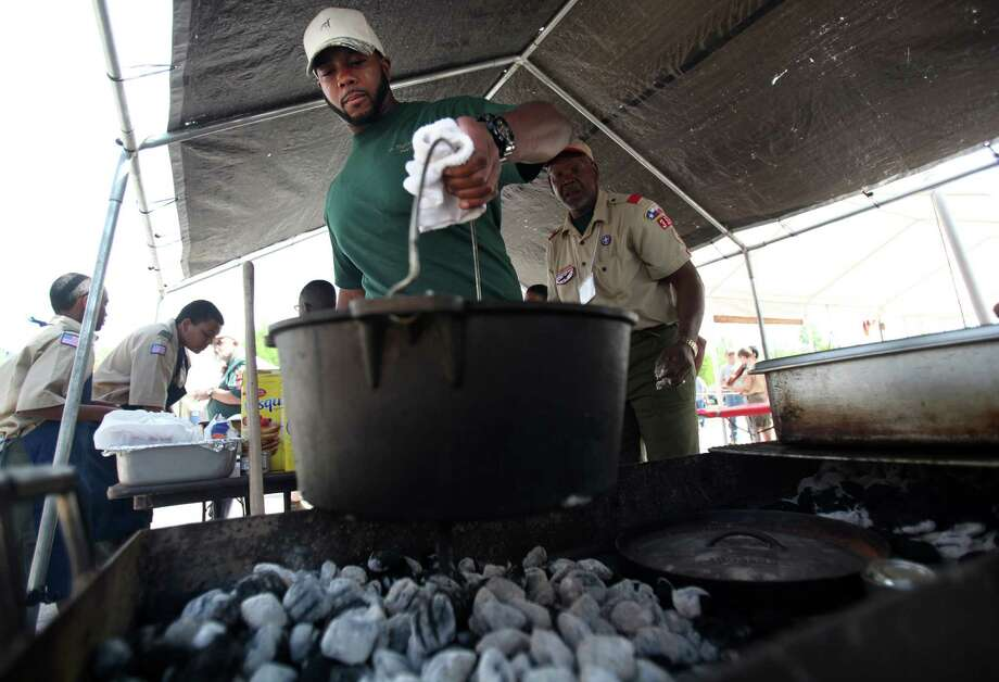 "Eagle Scout Michael James, 25, of Boy Scout Troop #352, places a batch of pineapple biscuits in a dutch oven over hot coals during the Scout Fair 2013, ""The Best Scout Fair on Earth"", at Reliant Arena on Saturday, April 13, 2013, in Houston. Photo: Mayra Beltran, Houston Chronicle / © 2013 Houston Chronicle"