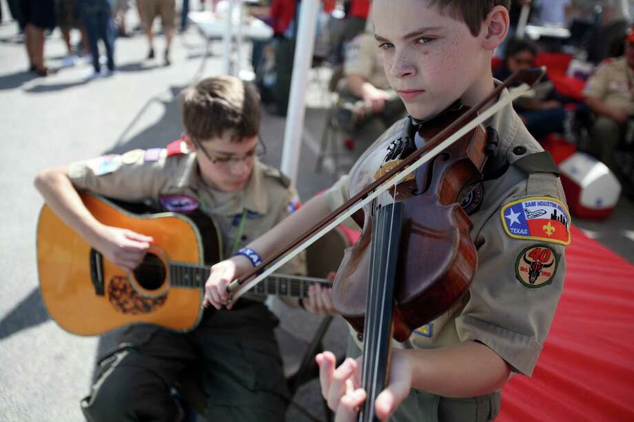 "Stephen Vannoy, 15, plays the guitar while brother Daniel Vannoy, 13, plays the fiddle in front of Boy Scout Troop #40 booth during the Scout Fair 2013, ""The Best Scout Fair on Earth"", at Reliant Arena on Saturday, April 13, 2013, in Houston. Photo: Mayra Beltran, Houston Chronicle / © 2013 Houston Chronicle"