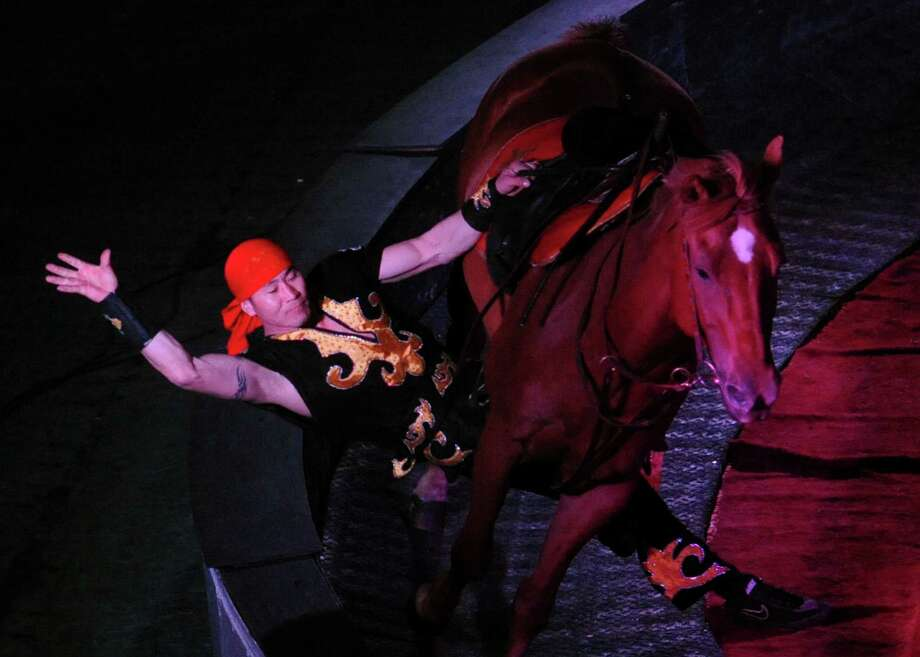 A Cossack Rider performs a trick on a horse at the Piccadilly Circus at Danbury Arena in Danbury, Conn. on Saturday, April 13, 2013.  The show featured riders, acrobats, motorcycles, clowns and much more.  The show is also being performed Sunday at 1:00, 3:30 and 6:00. Photo: Tyler Sizemore / The News-Times