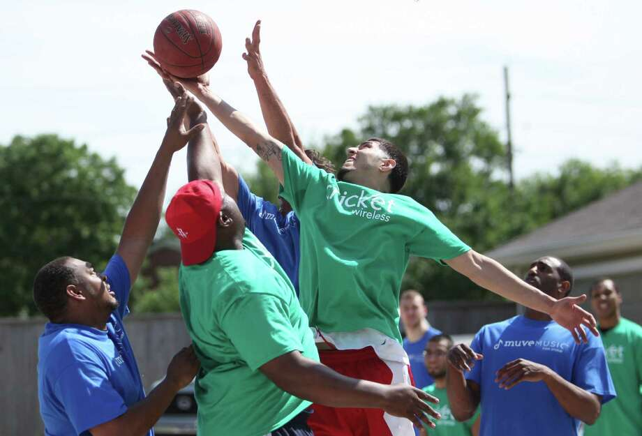 Mitchell Henry, 40, Sylvester Joseph, and Christian Lopez, 20, reach for the basketball during the Cricket & Rockets Driveway Challenge on Saturday, April 13, 2013, in Houston. Photo: Mayra Beltran, Houston Chronicle / © 2013 Houston Chronicle