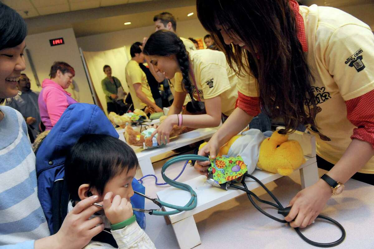 Hao Le, 6, of Albany gets help with his bears checkup by first year medical student Nancy Lin as Albany Medical College students hosted their 18th Annual Teddy Bear Hospital Day on Saturday April 13, 2013 in Albany, N.Y. (Michael P. Farrell/Times Union)