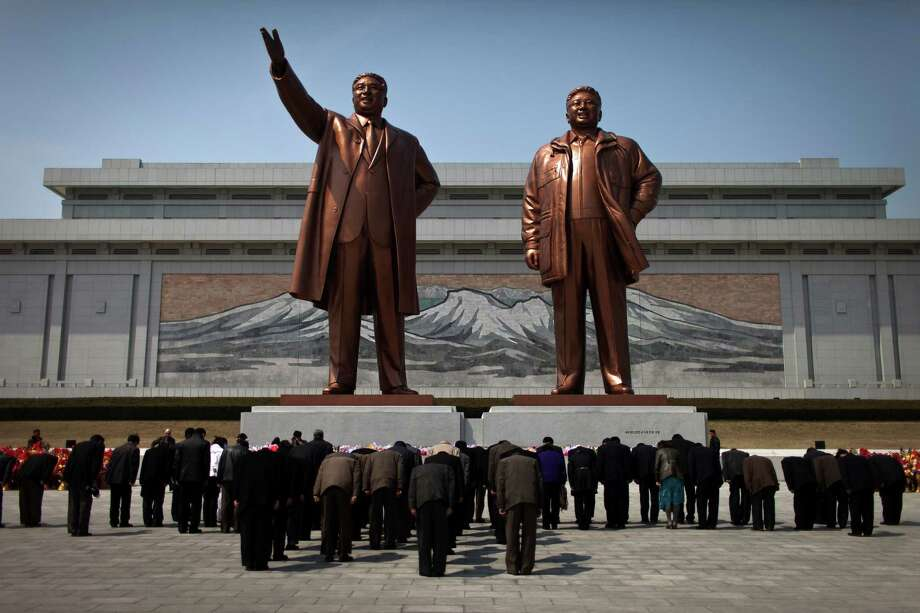 North Koreans bow to statues of late leaders Kim Il Sung, left, and Kim Jong Il in Pyongyang on Saturday as the U.S. secretary of state held talks in China. Photo: Alexander F. Yuan, STF / AP