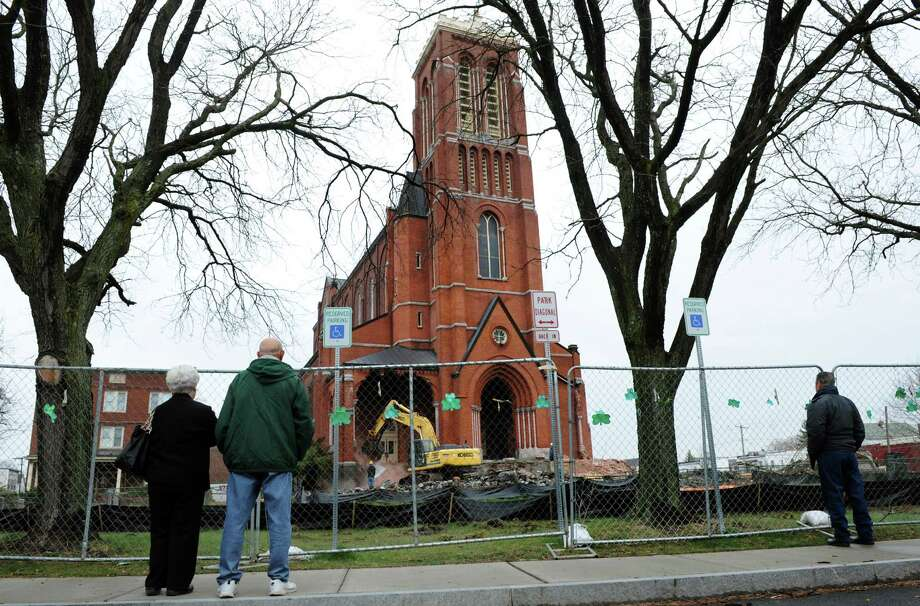 Bystanders watch demolition crews knock down the left side porch on Saturday, April 13, 2013, at St. Patrick's Roman Catholic Church in Watervliet, N.Y. (Cindy Schultz / Times Union) Photo: Cindy Schultz