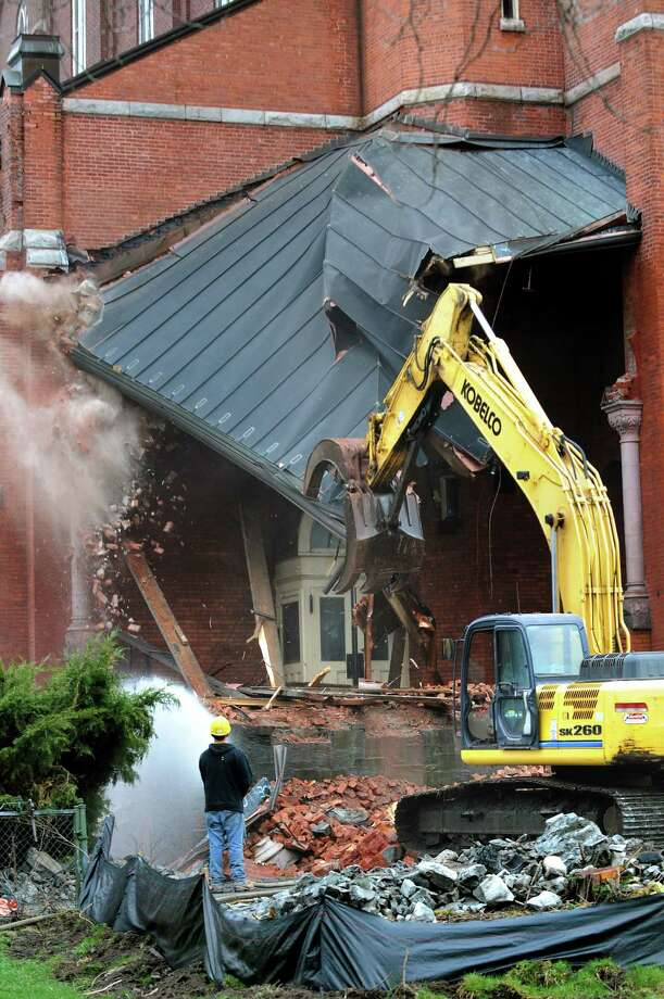 Demolition crews pull off the copper roof from the left side porch on Saturday, April 13, 2013, at St. Patrick's Roman Catholic Church in Watervliet, N.Y. (Cindy Schultz / Times Union) Photo: Cindy Schultz