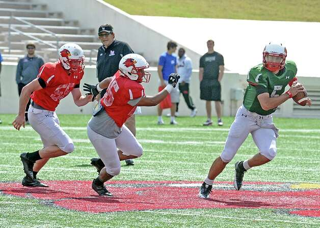 Quarterback Ryan Mossakowski, #5, sprints to get away from Logan Moss, #55, and Melvin Smith, #25, during the Lamar University football scrimmage at Provost-Umphrey Stadium on Saturday, April 13, 2013. Photo taken: Randy Edwards/The Enterprise