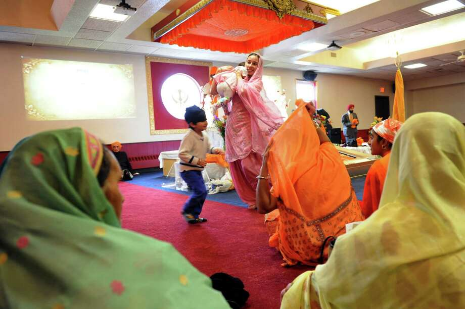 Ramandeep Kaur of Clifton Park, center, collects her daughter, Eknoor Sandhu, 11 months, during the inaugural services of a new Sikh temple on Saturday, April 13, 2013, at Capital Gurudwara in Rensselaer, N.Y. (Cindy Schultz / Times Union) Photo: Cindy Schultz / 10021971A