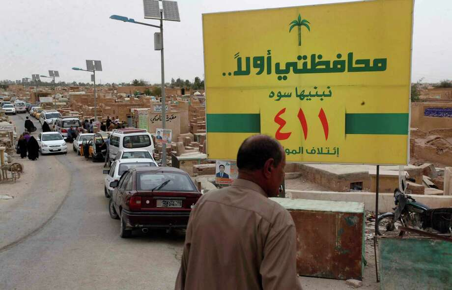 In this picture taken on April 12, 2013, people walk past an election poster at the cemetery in the Shiite holy city of Najaf, 100 miles (160 kilometers) south of Baghdad, Iraq. Voters head to the polls next week for the first time since the U.S. military withdrawal, marking a key test for Prime Minister Nouri al-Maliki's political bloc and for the security forces under his command that are charged with keeping voters safe. (AP Photo/ Alaa al-Marjani) Photo: Alaa Al-Marjani, STR / AP