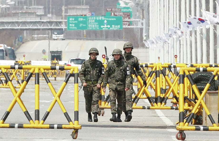 South Korean army soldiers patrol on Unification Bridge in Paju, South Korea, near the border village of Panmunjom, Saturday, April 13, 2013. As the world watches to see what North Korea's next move will be in a high-stakes game of brinksmanship with the United States, residents of its capital aren't hunkering down in bunkers and preparing for the worst. Instead, they are out on the streets en masse getting ready for the birthday of national founder Kim Il Sung — the biggest holiday of the year. The festivities leading up to Kim's birthday come amid fears that North Korea may be planning to test launch a new missile in retaliation for what it claims are provocative war games by U.S. and South Korean troops just across the Korean border. (AP Photo/Ahn Young-joon) Photo: Ahn Young-joon