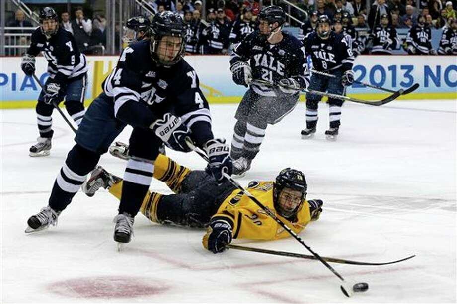 Yale's Rob O'Gara (4) clears the puck after colliding with Quinnipiac's Matthew Peca (20) during the first period of the NCAA Frozen Four men's college hockey national championship game in Pittsburgh Saturday, April 13, 2013. (AP Photo/Gene Puskar)