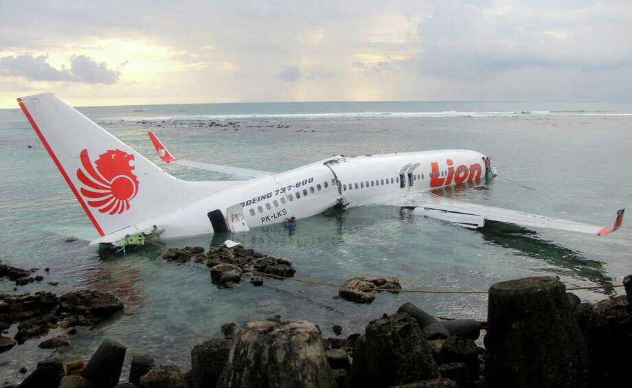 In this photo released by Indonesian Police, the wreckage of a crashed Lion Air plane sits on the water near the airport in Bali, Indonesia on Saturday, April 13, 2013. The plane carrying more than 100 passengers and crew overshot a runway on the Indonesian resort island of Bali on Saturday and crashed into the sea, injuring nearly two dozen people, officials said. (AP Photo/Indonesian Police)