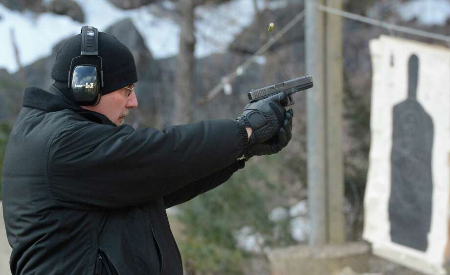 Albany County Corrections officer Frank Barger fires his service weapon for their annual certification  March 14, 2013 at their range in Bethlehem, N.Y.  (Skip Dickstein/Times Union) Photo: SKIP DICKSTEIN / 10021564A