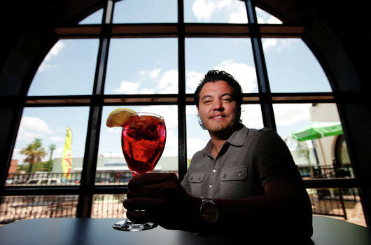 Review of Deco Pizzeria on Tuesday, June 28, 2011. Featured dishes: Chicken wings, hero sub, meatball sub, fruit pizza and sangria. Pictured is owner Jacob Valenzuela with a glass of his popular sangria. Kin Man Hui/kmhui@express-news.net Photo: KIN MAN HUI, San Antonio Express-News / San Antonio Express-News