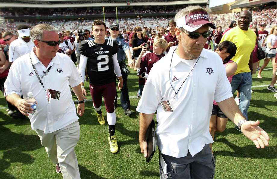Texas A&M Aggies quarterback Johnny Manziel (2) is escorted off the field as the fans swarmed onto the field after the Texas A&M University's Maroon & White, spring game at Kyle Field, Saturday, April 13, 2013, in College Station. Photo: Karen Warren, Houston Chronicle / © 2013 Houston Chronicle