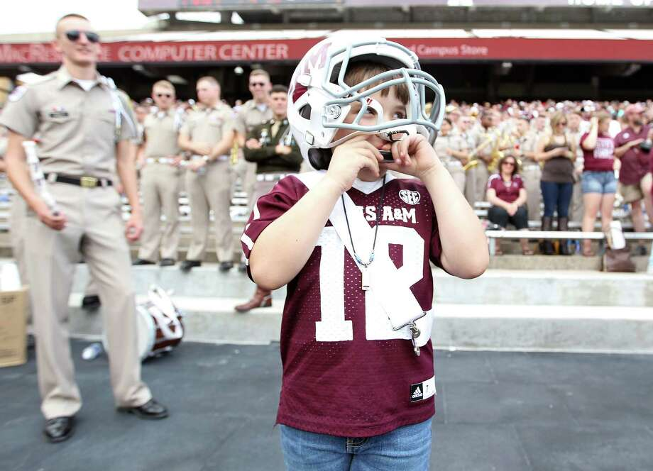 Yosef Herrera, 6, of McAllen, wears an A&M football helmet as he plays his harmonica while the Aggie band plays a song during the first half of the Texas A&M University's Maroon & White, spring game at Kyle Field, Saturday, April 13, 2013, in College Station. Photo: Karen Warren, Houston Chronicle / © 2013 Houston Chronicle