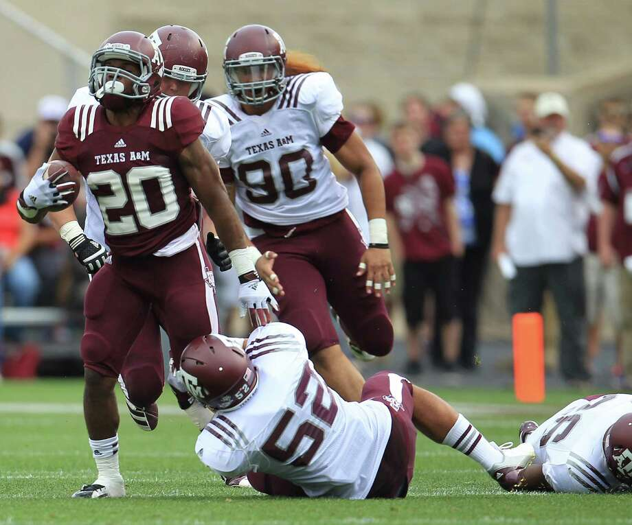 Texas A&M Aggies running back Trey Williams (20) tries to avoid the tackle of Brett Wade (52) during the first half of the Texas A&M University's Maroon & White, spring game at Kyle Field, Saturday, April 13, 2013, in College Station. Photo: Karen Warren, Houston Chronicle / © 2013 Houston Chronicle