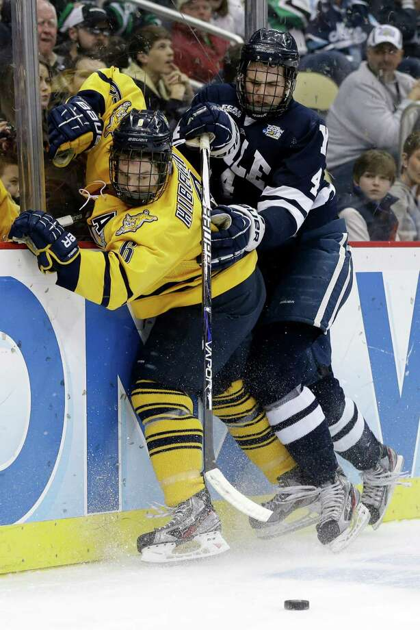 Quinnipiac's Cory Hibbeler (6) collides with Yale's Rob O'Gara (4) during the first period of the NCAA Frozen Four men's college hockey national championship game in Pittsburgh on Saturday, April 13, 2013. (AP Photo/Gene Puskar) Photo: Gene Puskar, Associated Press / AP
