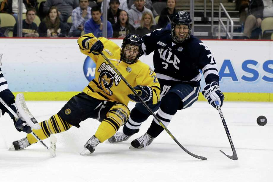 Quinnipiac's Matthew Peca (20) and Yale's Matt Killian (7) go after a rebound during the first period of the NCAA Frozen Four men's college hockey national championship game in Pittsburgh on Saturday, April 13, 2013. (AP Photo/Gene Puskar) Photo: Gene Puskar, Associated Press / AP