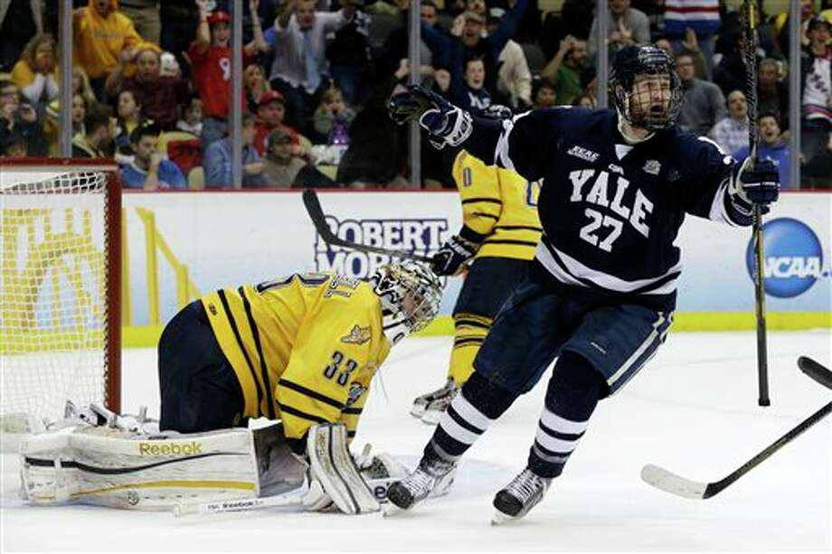 Yale's Charles Orzetti (27) celebrates a first-period goal by teammate Clinton Bourbonais (not shown) past Quinnipiac goalie Eric Hartzell (33) during the first period of the NCAA men's college hockey national championship game in Pittsburgh, Saturday, April 13, 2013. (AP Photo/Gene Puskar)