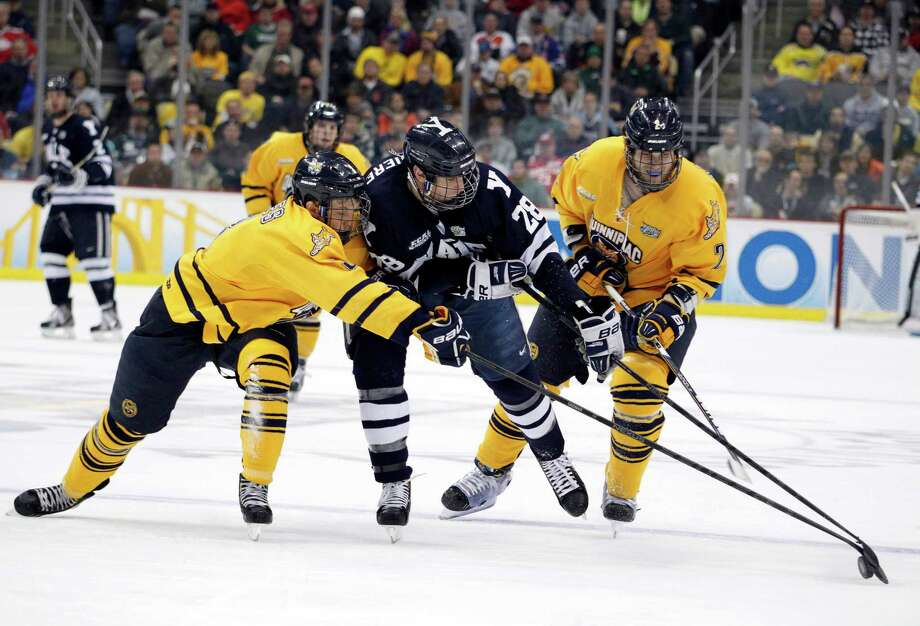 PITTSBURGH, PA - APRIL 13:  Antoine Laganiere #28 of the Yale Bulldogs skates between Zach Davies #3 and Mike Dalhuisen #2 of the Quinnipiac Bobcats during the game at Consol Energy Center on April 13, 2013 in Pittsburgh, Pennsylvania.  (Photo by Justin K. Aller/Getty Images) Photo: Justin K. Aller, Getty Images / 2013 Getty Images