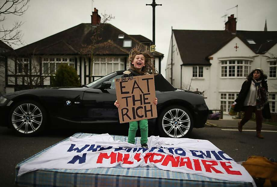"A taste of money:In North London, 8-year-old Lucien Shalmy-Freeman proposes wealth-based cannibalism as UK UNCUT supporters protest government changes to the welfare system and a proposed ""bedroom tax."" The anti-austerity campaigners gathered outside the Highgate home of Lord Freud after promising to target the home of a ""well-known millionaire."" Photo: Dan Kitwood, Getty Images"