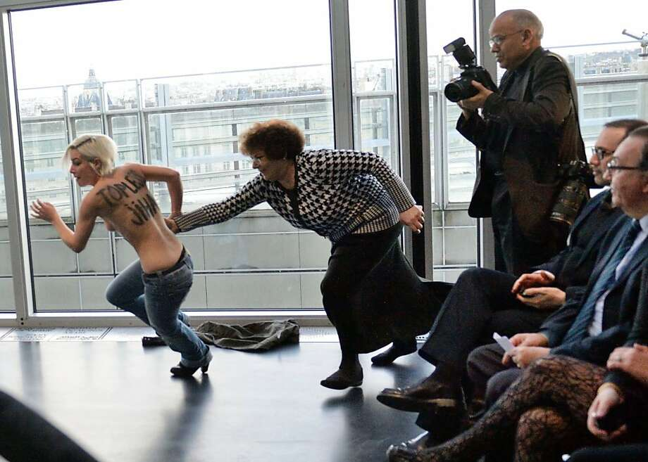 Don't get up, gents on the right. The lady can handle this situation all by herself: A Femen protester evades capture after interrupting a press conference by Tunisian President Moncef Marzouki in Paris. Photo: Eric Feferberg, AFP/Getty Images