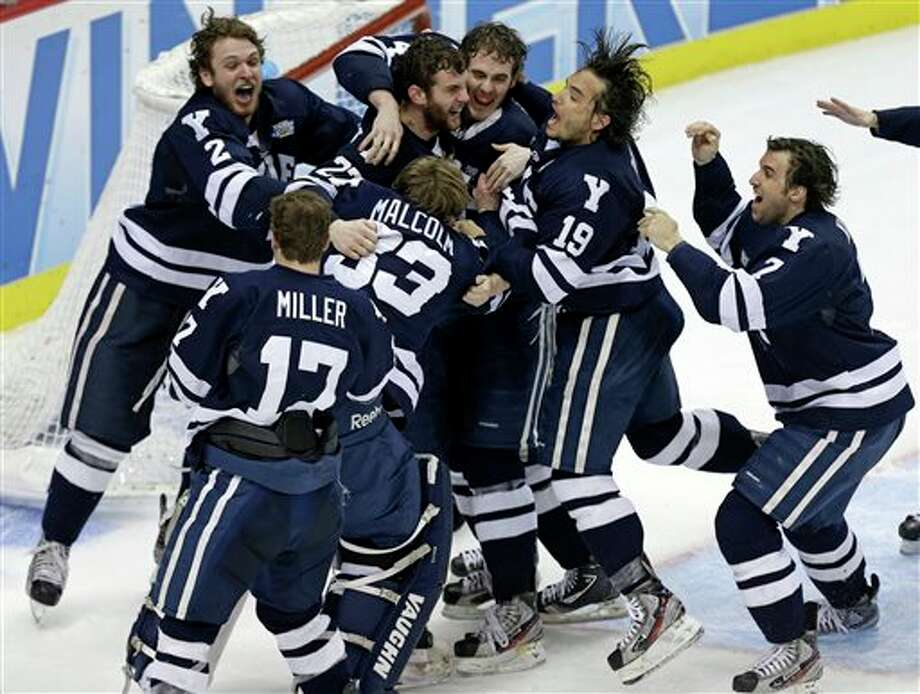 Yale goalie Jeff Malcolm (33) is swarmed by teammates after shutting out Quinnipiac 4-0 to win the NCAA men's college hockey Frozen Four national championship game in Pittsburgh, Saturday, April 13, 2013. (AP Photo/Gene Puskar)