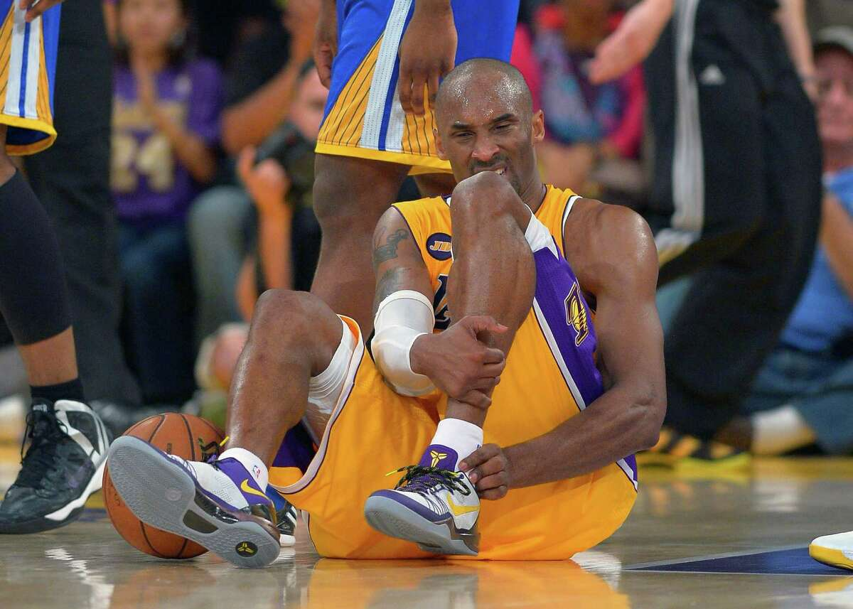 The Lakers' Kobe Bryant grimaces after being injured during the second half of their NBA basketball game against the Golden State Warriors, Friday, April 12, 2013, in Los Angeles. The Lakers won 118-116. (AP Photo/Mark J. Terrill)